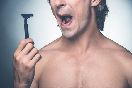 expressing negativity: He needs a new razor. Close-up of young shirtless man holding razor and expressing negativity while standing against grey background