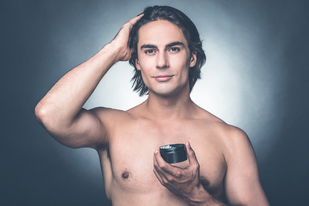hair gel: Used to look perfect. Portrait of young shirtless man looking at camera while applying hair gel and standing against grey background Stock Photo