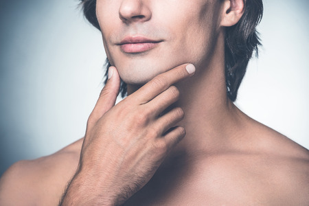 Feeling clean and fresh. Close-up of handsome young shirtless man holding hand on chin while standing against grey background Stock Photo