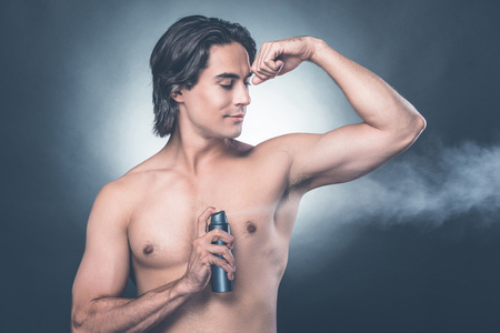 Getting fresh. Handsome young shirtless man spraying deodorant while standing against grey background Stock Photo