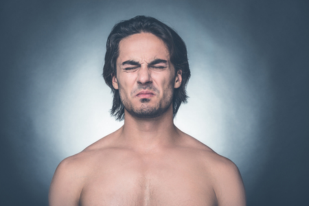 expressing negativity: Feeling disgust. Portrait of young shirtless man keeping eyes closed and expressing negativity while standing against grey background Stock Photo