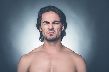 expresiones faciales: Sintiendo asco. Retrato de hombre joven sin camisa mantener los ojos cerrados y expresar negatividad de pie sobre fondo gris