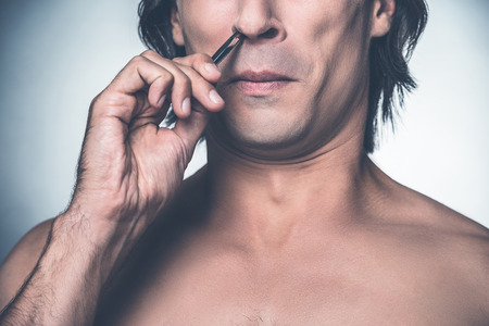 metrosexual: Painful procedure. Close-up of young shirtless man plucking his hair from nose and grimacing while standing against grey background Stock Photo