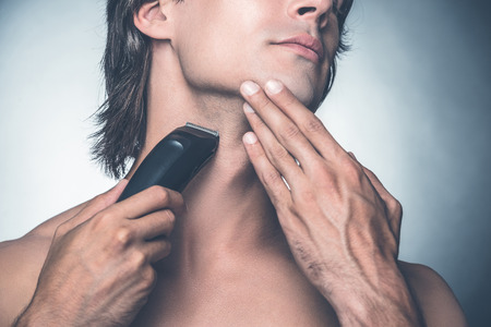 electric razor: Shaving with electric razor. Close-up of handsome young shirtless man shaving with electric razor while standing against grey background
