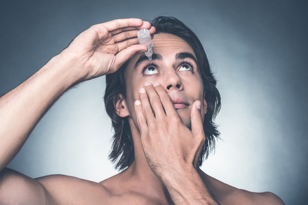 Taking good care of his eyes. Portrait of young shirtless man putting drops into eyes while standing against grey background