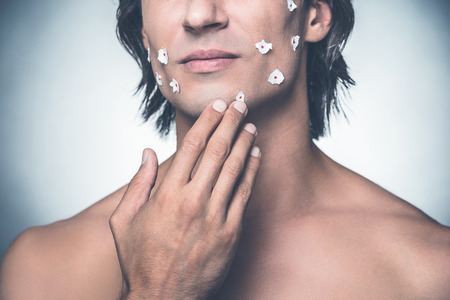 expressing negativity: Really bad shave. Close-up of frustrated young shirtless man touching his face and expressing negativity while standing against grey background