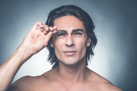 tweezing: This is painful. Portrait of young shirtless man tweezing eyebrows and expressing negativity while standing against grey background