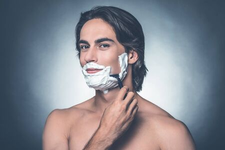 metrosexual: Morning shave. Handsome young shirtless man shaving and looking at camera while standing against grey background