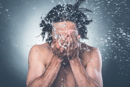 metrosexual: Washing up. Young shirtless man washing face with water splashing around him