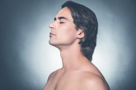 Fresco y limpio. Vista lateral del hombre joven sin camisa mantener los ojos cerrados y buscando la calma mientras está de pie contra el fondo gris