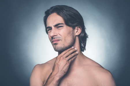 expressing negativity: Feeling pain in throat. Portrait of young shirtless man expressing negativity while touching his neck and standing against grey background