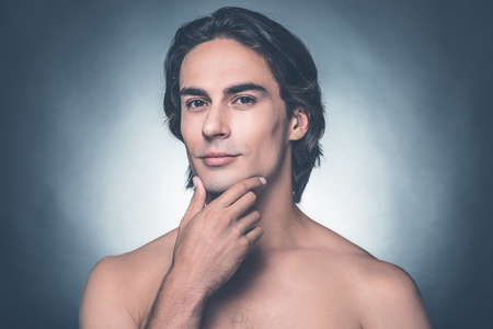 metrosexual: Feeling fresh after shaving. Portrait of handsome young shirtless man looking at camera and holding hand on chin while standing against grey background