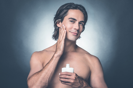 aftershave: Feeling fresh and clean. Portrait of handsome young shirtless man looking at camera and applying aftershave lotion on face while standing against grey background