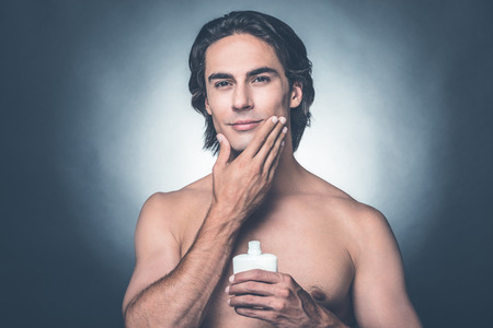 Feeling fresh after shaving. Portrait of handsome young shirtless man looking at camera and applying aftershave lotion on face while standing against grey background Stock Photo