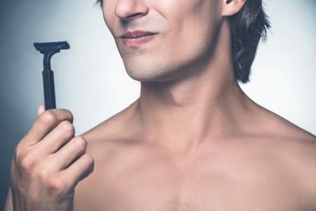 expressing negativity: Need a new razor? Close-up of young shirtless man holding razor and expressing negativity while standing against grey background