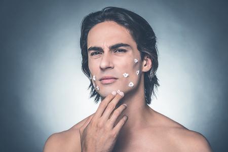 visage homme: Mauvais rasage. Un homme sans chemise frustré qui touche son visage et qui exprime la négativité tout en restant debout contre un fond gris