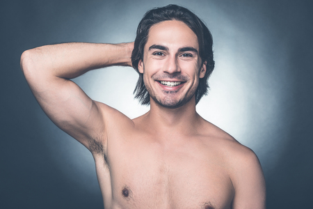looking good: Looking good and feeling great. Portrait of young shirtless man looking at camera and smiling while standing against grey background Stock Photo