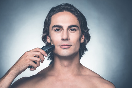 electric razor: Safe shaving. Handsome young shirtless man shaving with electric razor and looking at camera while standing against grey background Stock Photo
