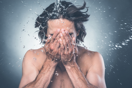 refreshed: Getting refreshed. Young shirtless man washing face with water splashing around him Stock Photo