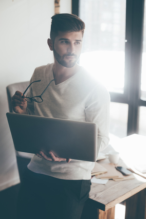 man with laptop: Thinking about solution. Thoughtful young man carrying laptop and eyeglasses while leaning at the desk in office and looking away Stock Photo