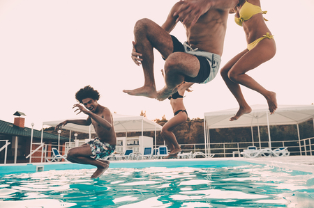 youth group: Pool fun. Group of beautiful young people looking happy while jumping into the swimming pool together Stock Photo
