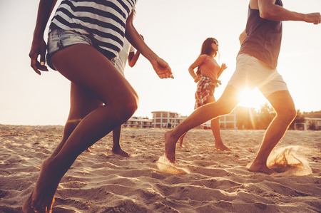 feeling happy: Feeling energy inside. Group of young cheerful people running along the beach and looking happy