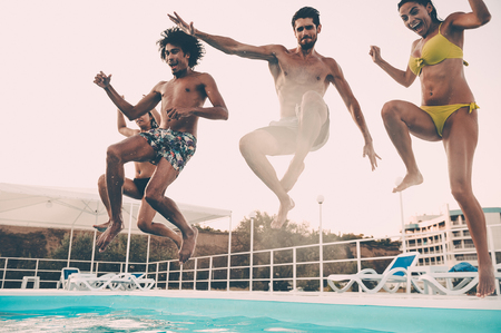 Jumping to the pool. Group of beautiful young people looking happy while jumping into the swimming pool together Stock Photo