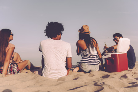 Relaxing with friends. Rear view of four cheerful young people spending nice time together while sitting on the beach and drinking beer Stock Photo