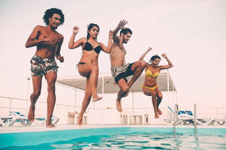 Time to get refreshed. Group of beautiful young people looking happy while jumping into the swimming pool together Stock Photo