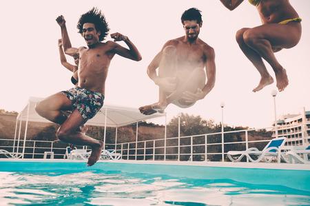 grupo de hombres: Tiempo de piscina. Grupo de jóvenes hermosas que parece feliz mientras que salta a la piscina juntos