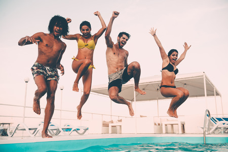 Pool fun. Group of beautiful young people looking happy while jumping into the swimming pool together Stock Photo