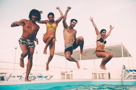 Zwembad plezier. Groep mooie jonge mensen kijkt gelukkig terwijl ze samen in het zwembad springen