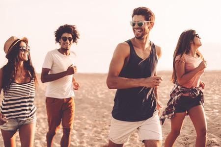자유를 누리고 있습니다. 젊은 쾌활한 사람들이 해변을 따라 실행하고 행복한 찾고 그룹