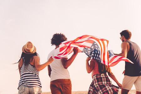 Freunde mit amerikanischer Flagge. Rückansicht von vier jungen Menschen mit amerikanischen Flagge beim Laufen im Freien