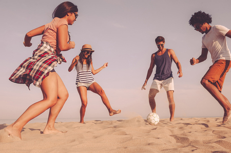 Just having fun. Group of cheerful young people playing with soccer ball on the beach with sea in the background