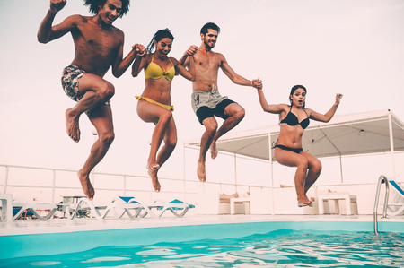 Enjoying pool party. Group of beautiful young people looking happy while jumping into the swimming pool together Stock Photo