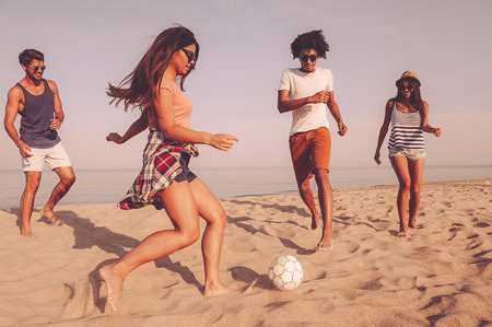 Enjoying time with best friends. Group of cheerful young people playing with soccer ball on the beach with sea in the background