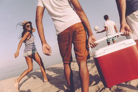 ビーチで友達。一方、プラスチックのクーラーを運ぶ 2 つの男性海にビーチを歩いて陽気な若い人たちの後姿