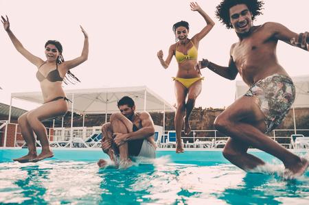 Zwemfeest. Groep mooie jonge mensen die gelukkig terwijl samen het springen in het zwembad kijken Stockfoto