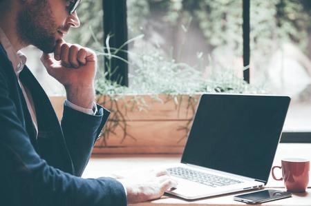 남자는 노트북에서 작동합니다. 노트북에 근무하는 안경에 확신 젊은 남자의 근접 사무실이나 카페에 앉아있는 동안