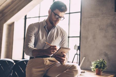 hombre escribiendo: Sólo inspirado. Seguro de joven en elegante casual desgaste escribiendo algo en su cuaderno mientras que se inclina en el escritorio en la oficina