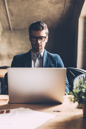 man with laptop: Man working on laptop. Confident young man in smart casual wear working on laptop while sitting at his working place in office Stock Photo