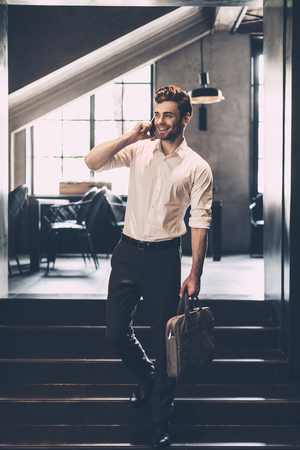 casual office: I will be in five minutes! Confident young man in smart casual wear talking on the mobile phone and smiling while holding bag and standing in office Stock Photo
