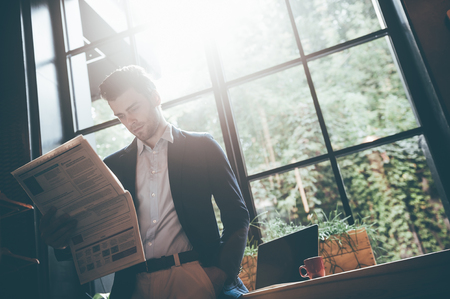 window sill: Reading latest news. Low angle view of confident young man reading fresh newspaper while leaning at the window sill in office or cafe Stock Photo