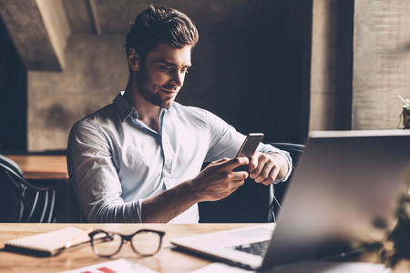 Good news from colleague. Confident young man in smart casual wear holding smart phone and looking at it while sitting at his working place in office Stok Fotoğraf