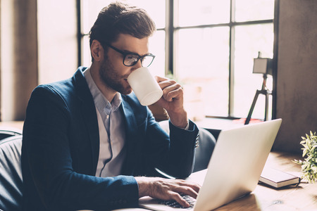 Enjoying fresh coffee at work. Confident young man in smart casual wear working on laptop and drinking some hot drink while sitting at his working place in office