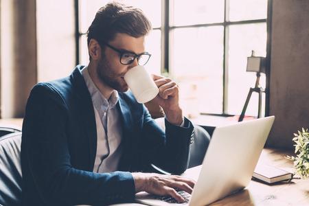 Genieten van verse koffie op het werk. Zekere jonge mens in slimme vrijetijdskleding werken op de laptop en het drinken van een aantal warme drank tijdens de vergadering op zijn werkplek in office