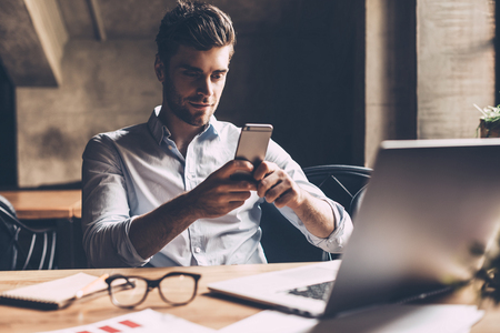 casual office: Texting to colleague. Confident young man in smart casual wear holding smart phone and looking at it while sitting at his working place in office