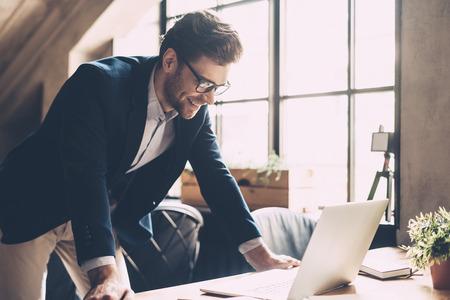 Beste oplossingen elke dag. Zekere jonge mens in slimme vrijetijdskleding kijken naar laptop en glimlachen terwijl staande in de buurt van zijn werkplaats in bureau
