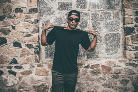Stay cool. Handsome young African man in casual clothes showing his black T-shirt while standing against the stoned wall outdoors